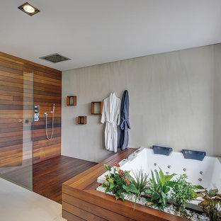 Modelo de cuarto de baño infantil, actual, sin sin inodoro, con jacuzzi, paredes grises, suelo de madera en tonos medios, encimera de madera, suelo marrón y ducha abierta