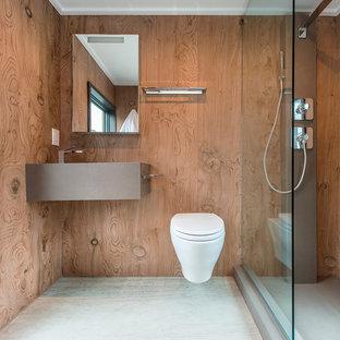 Inredning av ett modernt badrum för barn, med en öppen dusch, en vägghängd toalettstol, brun kakel, bruna väggar, betonggolv, ett väggmonterat handfat, grått golv och med dusch som är öppen