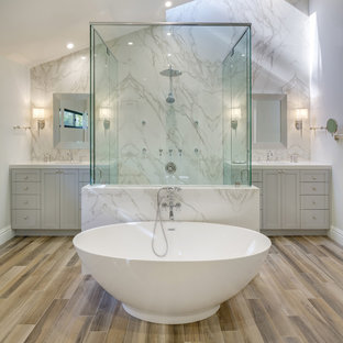 This is an example of a contemporary bathroom in Essex with recessed-panel cabinets, grey cabinets, a freestanding bath, white tiles, marble tiles, white walls, light hardwood flooring, an integrated sink, marble worktops, brown floors and a hinged door.