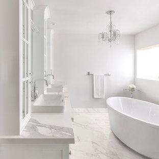 Foto de cuarto de baño principal, actual, con armarios tipo vitrina, puertas de armario blancas, bañera exenta, paredes blancas, suelo de mármol, lavabo encastrado, encimera de mármol y suelo blanco