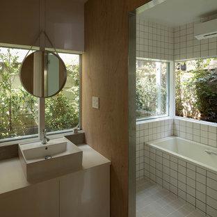 ストックホルムのコンテンポラリースタイルのおしゃれなマスターバスルーム (フラットパネル扉のキャビネット、白いキャビネット、アルコーブ型浴槽、白いタイル、ベージュの壁、ベッセル式洗面器) の写真