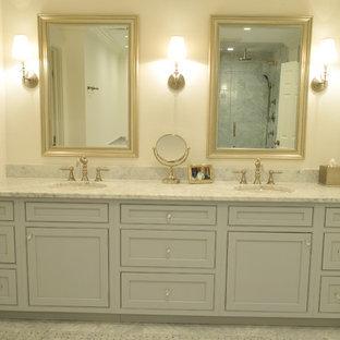 Modelo de cuarto de baño principal, clásico, de tamaño medio, con lavabo bajoencimera, armarios con paneles empotrados, puertas de armario grises, encimera de mármol, bañera encastrada, ducha esquinera, sanitario de dos piezas, baldosas y/o azulejos grises, baldosas y/o azulejos de piedra, paredes grises y suelo de mármol
