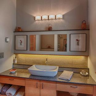 Modern inredning av ett stort badrum med dusch, med ett fristående handfat, släta luckor, skåp i mellenmörkt trä, bänkskiva i terrazo, en dusch i en alkov, en vägghängd toalettstol, beige kakel, porslinskakel, grå väggar och klinkergolv i porslin
