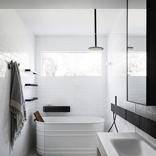 This is an example of a contemporary bathroom in Melbourne with flat-panel cabinets, dark wood cabinets, a freestanding tub, a curbless shower, white tile, subway tile, white walls, a drop-in sink, grey floor, an open shower and white benchtops.