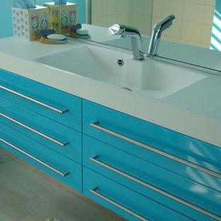 Immagine di una stanza da bagno design con lavabo integrato, ante lisce, ante turchesi, top in superficie solida, vasca da incasso, vasca/doccia, WC monopezzo e piastrelle in gres porcellanato