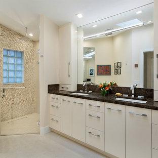 Неиссякаемый источник вдохновения для домашнего уюта: главная ванная комната среднего размера в современном стиле с плоскими фасадами, бежевыми фасадами, угловым душем, унитазом-моноблоком, бежевой плиткой, галечной плиткой, бежевыми стенами, полом из керамической плитки, врезной раковиной, столешницей терраццо, бежевым полом, душем с распашными дверями и черной столешницей