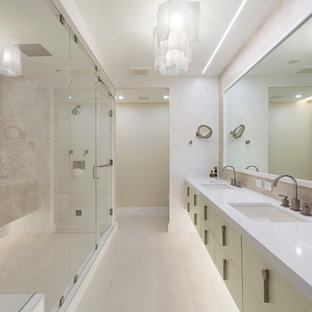 Mid-sized trendy master beige tile and porcelain tile beige floor and porcelain tile alcove shower photo in Miami with flat-panel cabinets, beige cabinets, an undermount sink, white countertops, a one-piece toilet, beige walls, solid surface countertops and a hinged shower door