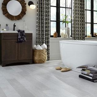 Foto di una grande stanza da bagno padronale design con consolle stile comò, ante in legno bruno, vasca freestanding, pavimento in vinile, lavabo sottopiano, pareti grigie, top in superficie solida e pavimento grigio
