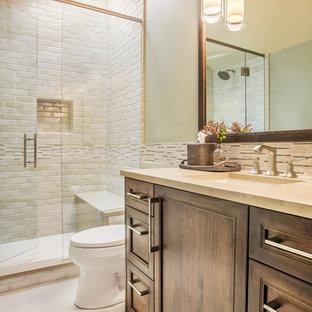Rustik inredning av ett mellanstort badrum med dusch, med ett undermonterad handfat, luckor med infälld panel, skåp i mörkt trä, bänkskiva i akrylsten, en dusch i en alkov, en toalettstol med hel cisternkåpa, beige kakel, keramikplattor, beige väggar, klinkergolv i keramik, vitt golv och dusch med gångjärnsdörr