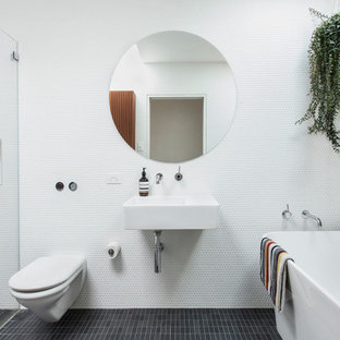 Contemporary master bathroom in Sydney with a freestanding tub, a curbless shower, white tile, white walls, a wall-mount sink, black floor, a single vanity and wood walls.