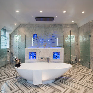 This is an example of a large contemporary wet room bathroom in Buckinghamshire with a freestanding bath, grey tiles, grey floors and a hinged door.