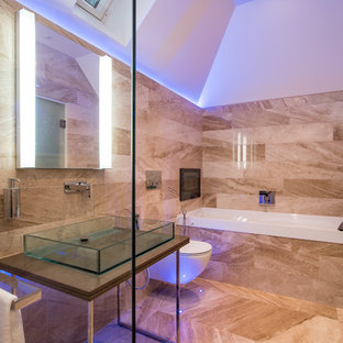 Photo of a medium sized contemporary bathroom in Buckinghamshire with an alcove bath, a wall mounted toilet, beige tiles, brown tiles, brown walls, a vessel sink, brown floors and brown worktops.