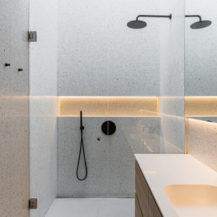 Inspiration for a modern bathroom in London with flat-panel cabinets, medium wood cabinets, a built-in shower, grey tiles, an integrated sink, grey floors, a hinged door, white worktops, a single sink and a floating vanity unit.