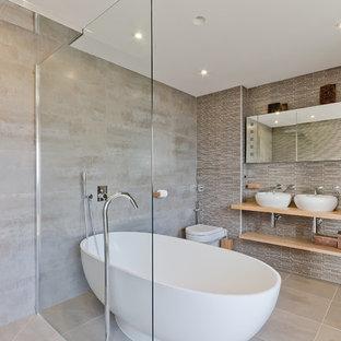 Inspiration för mellanstora moderna beige en-suite badrum, med ett fristående handfat, träbänkskiva, ett fristående badkar, en öppen dusch, en vägghängd toalettstol och med dusch som är öppen