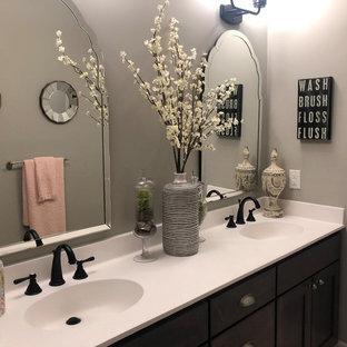 Foto de cuarto de baño infantil, clásico renovado, grande, con armarios con paneles empotrados, puertas de armario marrones, paredes grises, suelo de madera oscura, lavabo integrado, encimera de acrílico, suelo marrón y encimeras blancas