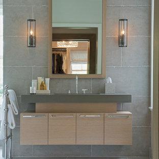 Diseño de cuarto de baño clásico renovado, de tamaño medio, con armarios con paneles lisos, puertas de armario de madera clara, baldosas y/o azulejos grises, paredes grises, suelo de cemento, lavabo bajoencimera y encimera de acrílico
