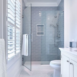 Photo of a medium sized classic family bathroom in New York with recessed-panel cabinets, white cabinets, an alcove shower, a two-piece toilet, blue tiles, ceramic tiles, white walls, marble flooring, a submerged sink, marble worktops, white floors and a hinged door.