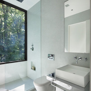 Foto på ett stort funkis badrum, med ett väggmonterat handfat, bänkskiva i rostfritt stål, en vägghängd toalettstol, vit kakel, glaskakel, vita väggar och mörkt trägolv