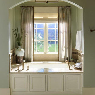 Inspiration for a timeless beige tile bathroom remodel in Nashville with white cabinets and an undermount tub