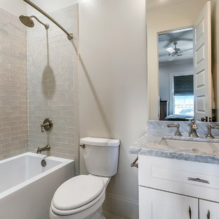 Example of a small trendy 3/4 gray tile and ceramic tile bathroom design in New Orleans with shaker cabinets, yellow cabinets, a two-piece toilet, gray walls, an undermount sink, marble countertops and gray countertops
