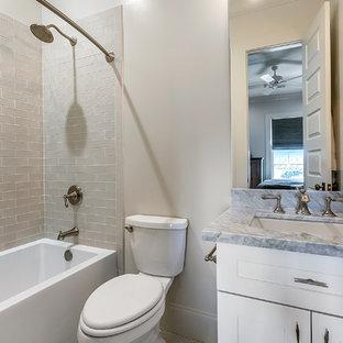 Idéer för att renovera ett litet funkis grå grått badrum med dusch, med skåp i shakerstil, gula skåp, ett badkar i en alkov, en dusch/badkar-kombination, en toalettstol med separat cisternkåpa, grå kakel, keramikplattor, grå väggar, ett undermonterad handfat, marmorbänkskiva och dusch med duschdraperi