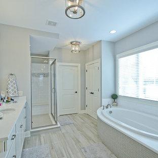 Imagen de cuarto de baño principal, tradicional renovado, grande, con lavabo bajoencimera, armarios con paneles empotrados, puertas de armario blancas, encimera de cuarcita, bañera encastrada, ducha esquinera, sanitario de dos piezas, baldosas y/o azulejos grises, baldosas y/o azulejos de porcelana, paredes grises y suelo de baldosas de porcelana