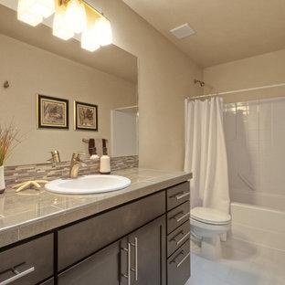 Idee per una stanza da bagno design di medie dimensioni con ante in stile shaker, ante in legno bruno, vasca sottopiano, vasca/doccia, WC monopezzo, piastrelle bianche, piastrelle a listelli, pareti beige, pavimento con piastrelle in ceramica, lavabo sottopiano e top piastrellato