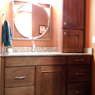Inspiration for a small timeless 3/4 beige floor bathroom remodel in St Louis with brown cabinets, raised-panel cabinets, pink walls, an undermount sink and granite countertops