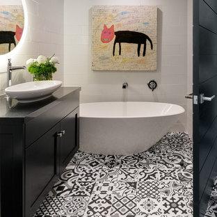 Modelo de cuarto de baño con ducha, de estilo americano, con armarios estilo shaker, puertas de armario negras, bañera exenta, baldosas y/o azulejos blancos, lavabo sobreencimera, suelo gris y encimeras negras