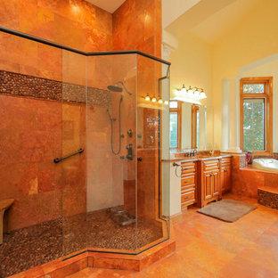 Ispirazione per una grande stanza da bagno padronale classica con lavabo sottopiano, ante con bugna sagomata, ante in legno bruno, top in granito, vasca da incasso, doccia doppia, WC monopezzo, piastrelle di ciottoli, pareti gialle, pavimento in travertino e piastrelle marroni
