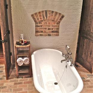 Immagine di una stanza da bagno padronale stile rurale con vasca con piedi a zampa di leone e pavimento in mattoni