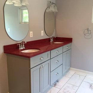Foto de cuarto de baño principal, contemporáneo, de tamaño medio, con armarios con paneles empotrados, puertas de armario grises, paredes grises, lavabo bajoencimera y encimeras rojas
