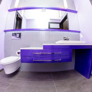 Foto di una stanza da bagno contemporanea di medie dimensioni con ante lisce, ante viola, piastrelle grigie, piastrelle di vetro, pareti bianche, pavimento in gres porcellanato, lavabo a bacinella, top in quarzo composito e pavimento marrone