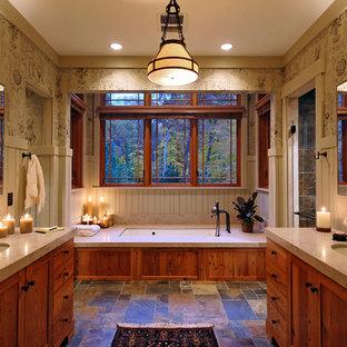 Imagen de cuarto de baño principal, rústico, con lavabo bajoencimera, armarios estilo shaker, puertas de armario de madera oscura, bañera encastrada sin remate, paredes multicolor y suelo de pizarra