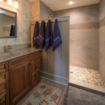 Alcove shower - traditional pebble tile floor alcove shower idea in Boston with an integrated sink, recessed-panel cabinets, gray walls and dark wood cabinets