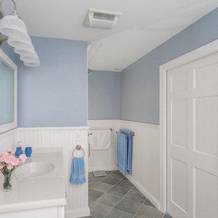 Modelo de cuarto de baño con ducha, clásico, pequeño, con armarios estilo shaker, puertas de armario blancas, sanitario de dos piezas, baldosas y/o azulejos grises, baldosas y/o azulejos de cerámica, paredes azules, suelo de baldosas de cerámica, lavabo integrado, encimera de laminado, bañera encastrada y ducha empotrada