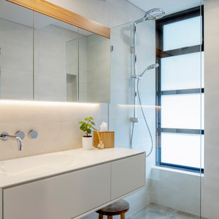 Photo of a contemporary bathroom in Sydney with flat-panel cabinets, white cabinets, a curbless shower, white tile, white walls, an integrated sink, grey floor, an open shower and white benchtops.