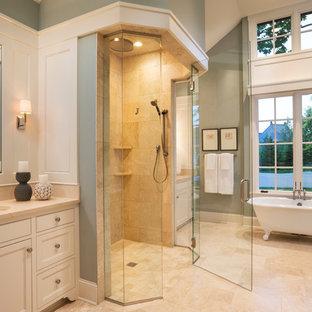 Cette image montre une petit douche en alcôve principale avec un lavabo encastré, un placard avec porte à panneau encastré, des portes de placard blanches, un plan de toilette en calcaire, une baignoire sur pieds, un carrelage beige, un mur bleu, un sol en calcaire, du carrelage en pierre calcaire, un sol beige, une cabine de douche à porte battante et un plan de toilette beige.