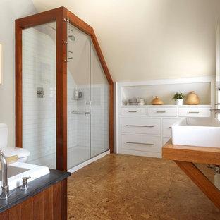 Свежая идея для дизайна: ванная комната в стиле кантри с плоскими фасадами, белыми фасадами, накладной ванной, угловым душем, унитазом-моноблоком, белой плиткой, плиткой кабанчик, бежевыми стенами, пробковым полом, столешницей из дерева, коричневым полом, душем с распашными дверями и раковиной с несколькими смесителями - отличное фото интерьера