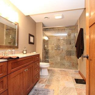 ミルウォーキーの中くらいのトランジショナルスタイルのおしゃれなバスルーム (浴槽なし) (シェーカースタイル扉のキャビネット、中間色木目調キャビネット、コンクリートの洗面台、マルチカラーのタイル、磁器タイル、アルコーブ型シャワー、ベージュの壁、アンダーカウンター洗面器、分離型トイレ、セラミックタイルの床、開き戸のシャワー、ベージュのカウンター) の写真
