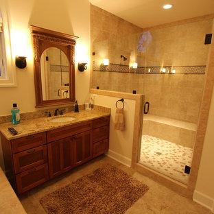 ワシントンD.C.の大きいトラディショナルスタイルのおしゃれなマスターバスルーム (シェーカースタイル扉のキャビネット、中間色木目調キャビネット、ドロップイン型浴槽、アルコーブ型シャワー、分離型トイレ、ベージュのタイル、セラミックタイル、ベージュの壁、セラミックタイルの床、アンダーカウンター洗面器、御影石の洗面台、ベージュの床、開き戸のシャワー、ベージュのカウンター) の写真