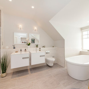 Design ideas for a contemporary bathroom in Sussex with flat-panel cabinets, white cabinets, a freestanding bath, grey tiles, white walls, a console sink and grey floors.