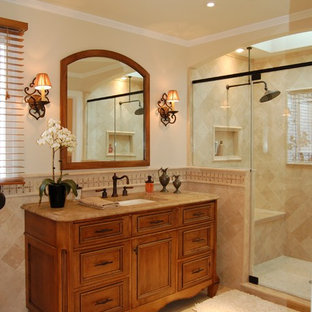 Example of a classic beige tile and travertine tile alcove shower design in Philadelphia with an undermount sink, recessed-panel cabinets and medium tone wood cabinets