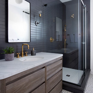 Example of a coastal black tile and black and white tile bathroom design in New York with flat-panel cabinets, dark wood cabinets and an undermount sink