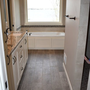 Drop-in bathtub - mid-sized traditional master beige tile and ceramic tile porcelain tile and brown floor drop-in bathtub idea in Minneapolis with shaker cabinets, white cabinets, a two-piece toilet, gray walls, an undermount sink and granite countertops