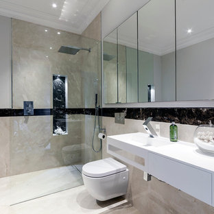 Design ideas for a medium sized contemporary ensuite bathroom in London with a walk-in shower, a wall mounted toilet, multi-coloured tiles, porcelain tiles, white walls, porcelain flooring, an integrated sink, solid surface worktops, beige floors and an open shower.