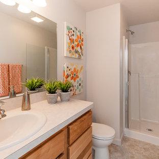 Foto de cuarto de baño contemporáneo, pequeño, con armarios estilo shaker, puertas de armario de madera clara, ducha empotrada, sanitario de dos piezas, paredes blancas, suelo vinílico, lavabo encastrado, encimera de laminado, suelo gris, ducha con puerta con bisagras y encimeras beige