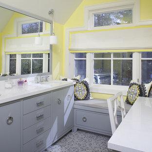 Cette photo montre une salle de bain tendance avec un plan de toilette en marbre, un lavabo encastré, des portes de placard grises, un mur jaune et un sol violet.