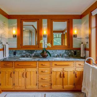 ポートランド(メイン)の中サイズのおしゃれなマスターバスルーム (アンダーカウンター洗面器、家具調キャビネット、中間色木目調キャビネット、御影石の洗面台、ドロップイン型浴槽、段差なし、分離型トイレ、ベージュのタイル、石タイル、マルチカラーの壁、ライムストーンの床、ベージュの床) の写真