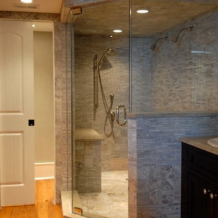 Mid-sized elegant master gray tile and matchstick tile medium tone wood floor corner shower photo in Orlando with recessed-panel cabinets, dark wood cabinets, a two-piece toilet, white walls, a drop-in sink and soapstone countertops